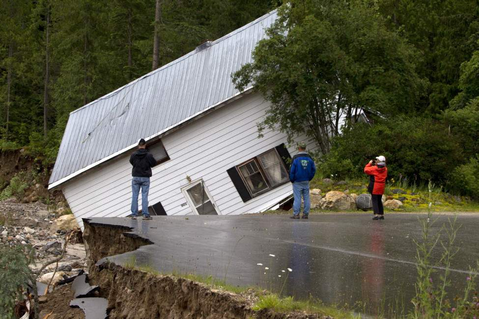 People look on as a house comes off its foundation in Two Mile just outside of Sicamous, B.C. Heavy rain falls, flooding and mudslides have caused the area to evacuated. (The Canadian Press / Jonathan Hayward)