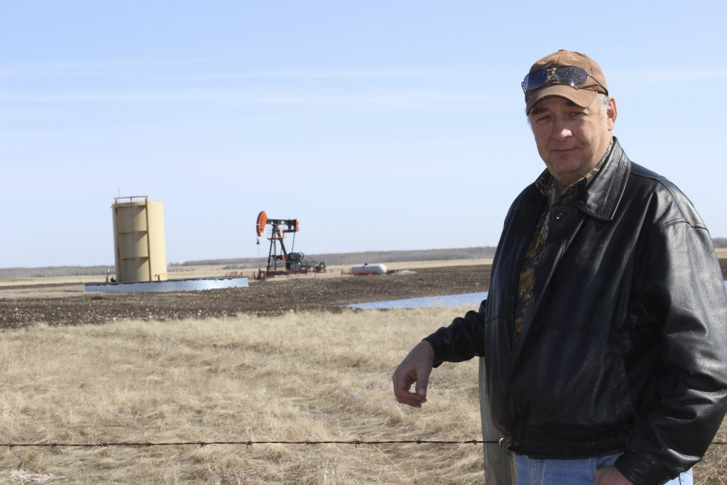 Roger Wilson, reeve of the RM of Birtle, in front of an oil well in the Birdtail Field from which the RM receives monthly royalties.