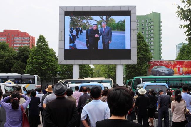 People watch a large screen at the main train station airing video of North Korean leader Kim Jong Un shaking hands with Singapore Prime Minister Lee Hsien Loong during his trip to Singapore in Pyongyang, North Korea, Monday, June 11, 2018. Kim is in Singapore to attend a summit with U.S. President Donald Trump. (AP Photo/Jon Chol Jin)