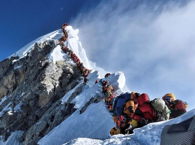 In this photo made on May 22, 2019, a long queue of mountain climbers line a path on Mount Everest. About half a dozen climbers died on Everest last week most while descending from the congested summit during only a few windows of good weather each May. (Nimsdai Project Possible via AP)