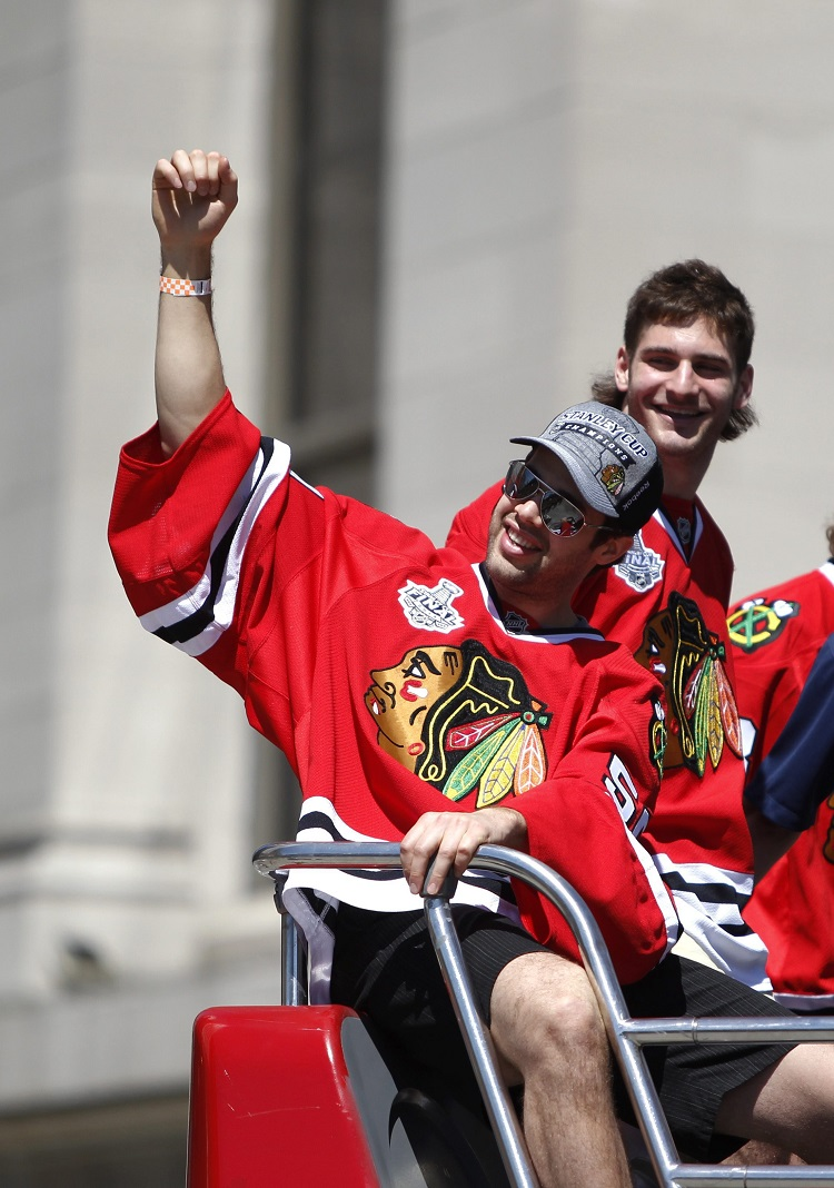 Chicago Blackhawks goalie Corey Crawford (left) and winger Brandon Saad wave and smile to the crowd.