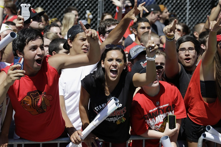 Fans cheer as buses carrying the Chicago Blackhawks roll by.