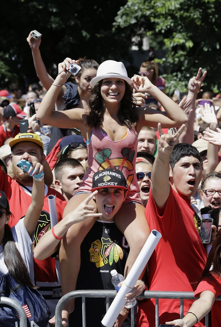 A fan gets a view from a higher vantage point along the parade route. (Nam Y. Huh / The Associated Press)