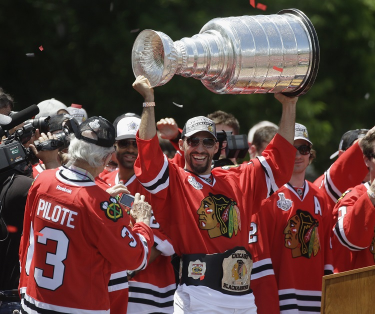 Chicago Blackhawks' Michal Rozsival hoists the Stanley Cup as Blackhawks legend Pierre Pilote prepares to take his picture.