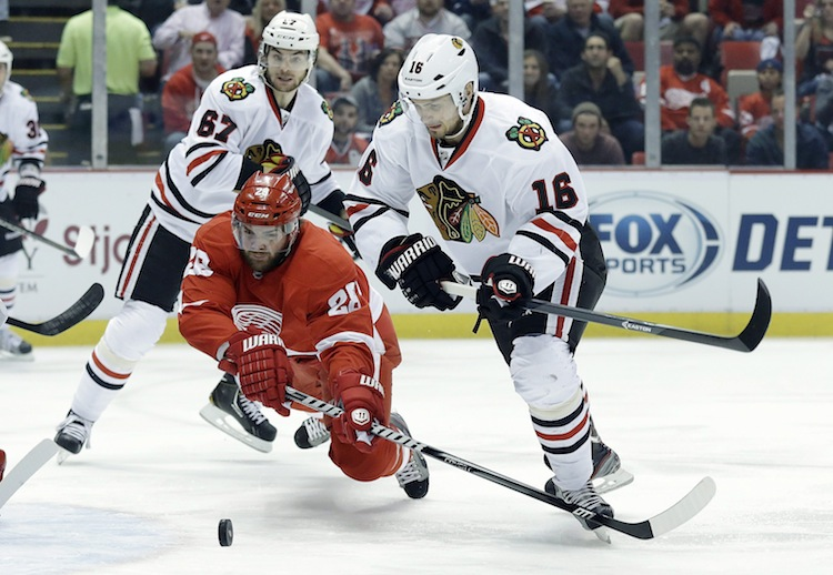 Detroit Red Wings defenceman Carlo Colaiacovo tries to clear the puck from Chicago Blackhawks forward Marcus Kruger during the first period.