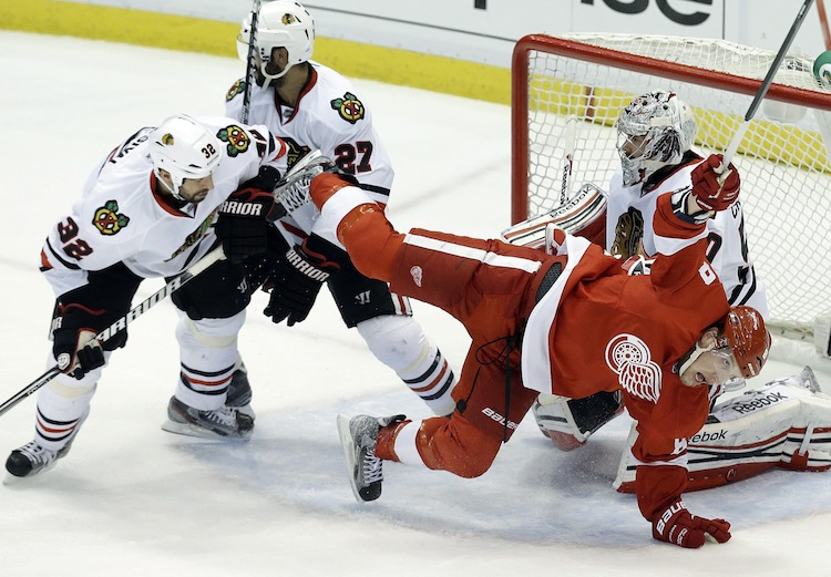 Detroit Red Wings left wing Justin Abdelkader (8) is checked by Chicago Blackhawks defenseman Michal Rozsival (32)in front of goalie Corey Crawford during the second period.