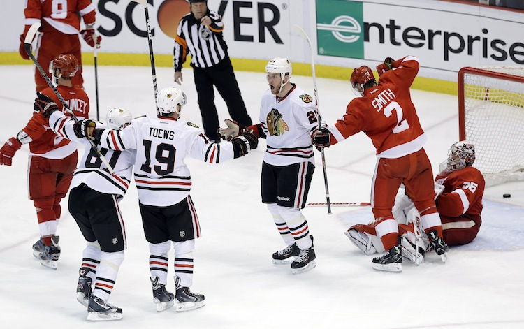 Chicago Blackhawks winger Bryan Bickell (29) celebrates scoring his third-period goal against the Detroit Red Wings with Marian Hossa (81) and Jonathan Toews (19) during the third period. the goal put the Blackhawks ahead 3-2.