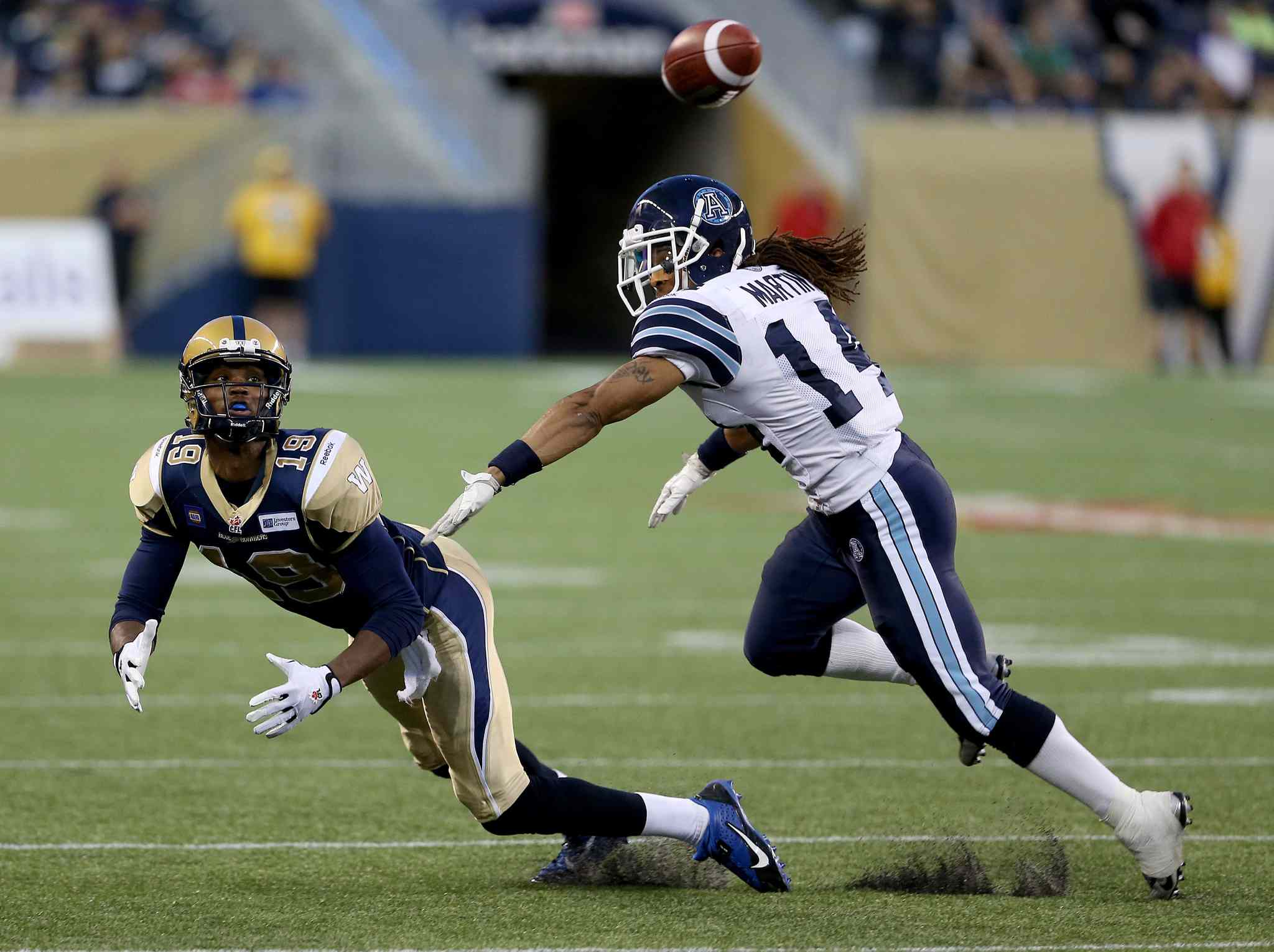 Bombers receiver Aaron Kelly dives for a pass behind Toronto's Andre Martin during the second half.