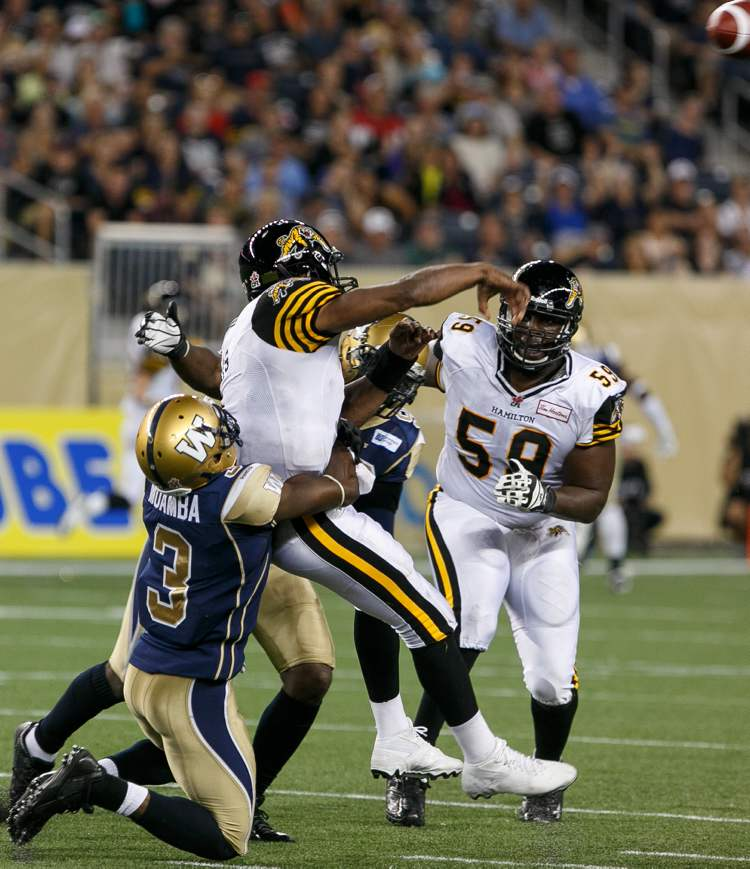 Hamilton Tiger-Cats' quarterback Henry Burris gets rid of the ball before Blue Bombers' Henoc Muamba can pull off a sack in the third quarter.