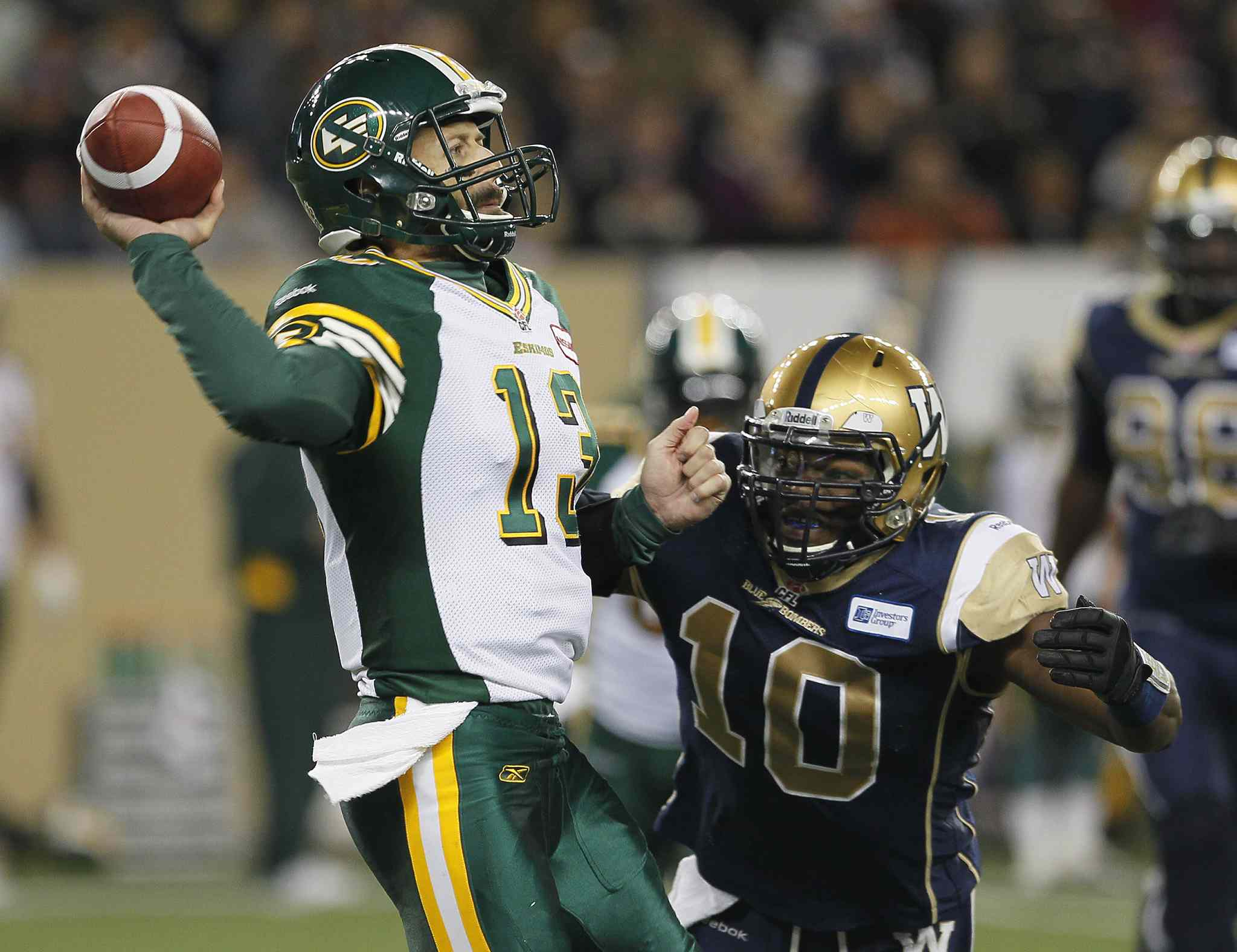 Edmonton Eskimos' quarterback Mike Reilly (left) gets a pass away under pressure from Winnipeg Blue Bombers' Henoc Muamba.