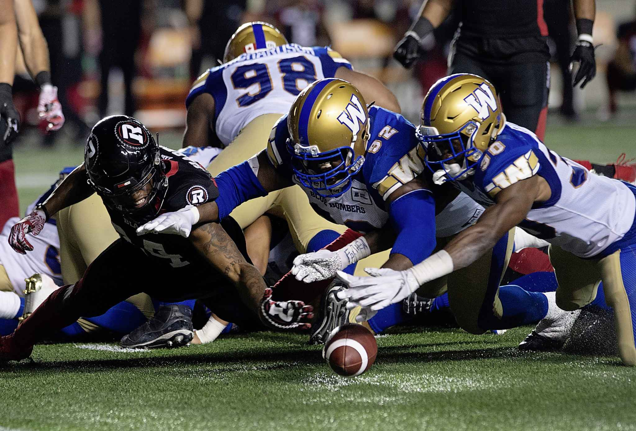 Winnipeg Blue Bombers defensive tackle Drake Nevis, centre, and teammate Winston Rose dive to recover a loose ball in Ottawa, last Friday. The Bombers D-corps hasn't allowed an offensive touchdown since the first week of the regular season.