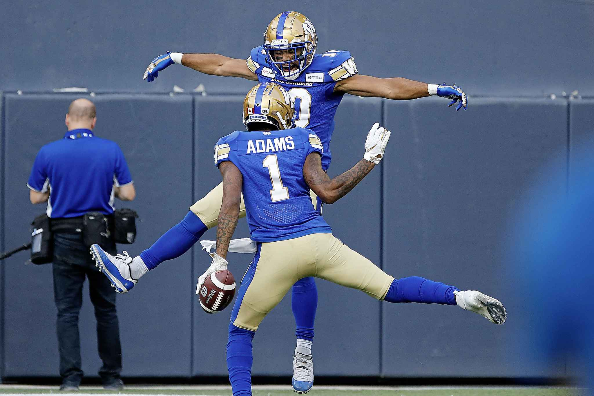 Blue Bombers' Darvin Adams and Nic Demski celebrate Adams' touchdown during the first half against the Toronto Argonauts, in Winnipeg, Friday.