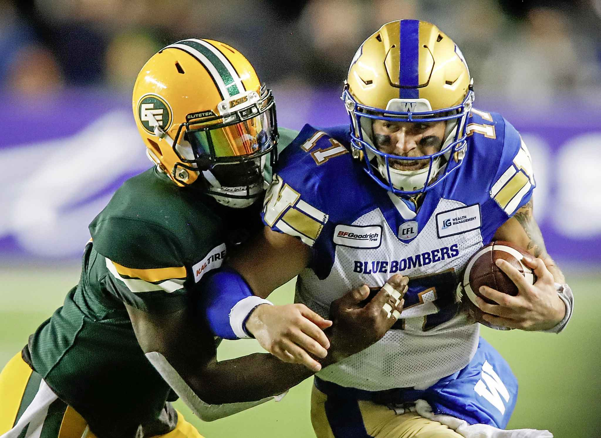 Winnipeg Blue Bombers quarterback Chris Streveler, right, runs the ball as Edmonton Eskimos' Larry Dean tries to tackle him during second half CFL football action in Edmonton, Friday.