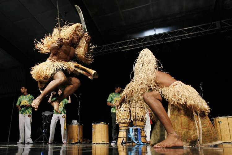 Costumed male dancers perform in the Brazilian pavilion.