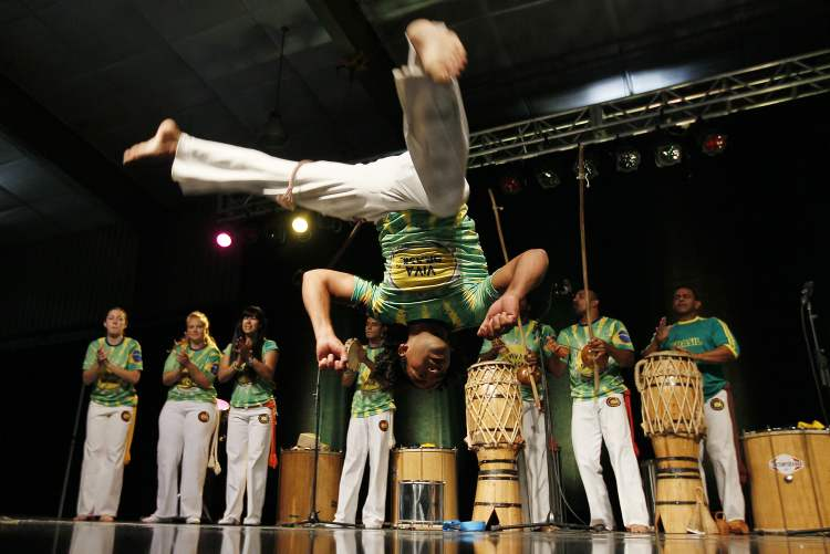 A dancer with Viva Brazil does a flip in the Brazilian pavilion.