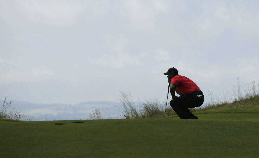 Tiger Woods of the US lines up a putt on the 13th green during the final round of the British Open Golf championship at the Royal Liverpool golf club, Hoylake, England, Sunday. (Jon Super / AP Photo)