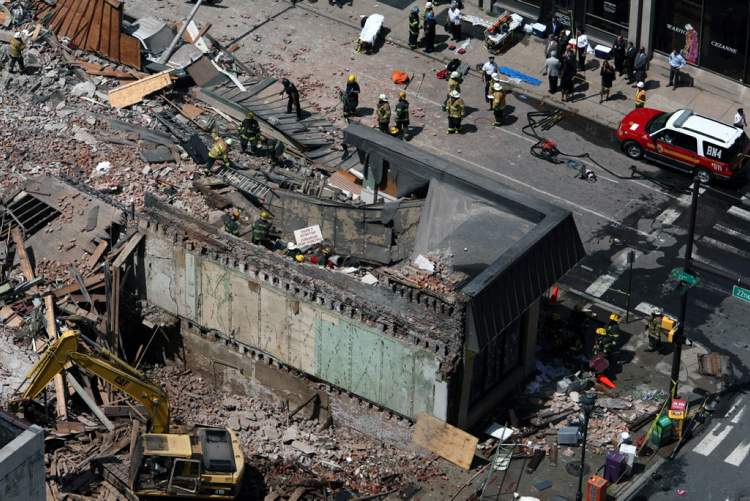 A window washer who had been working across the street for several days said the demolition crew left 30 feet of a dividing wall up with no braces and it compromised the integrity of the building. (Jacqueline Larma / The Associated Press)