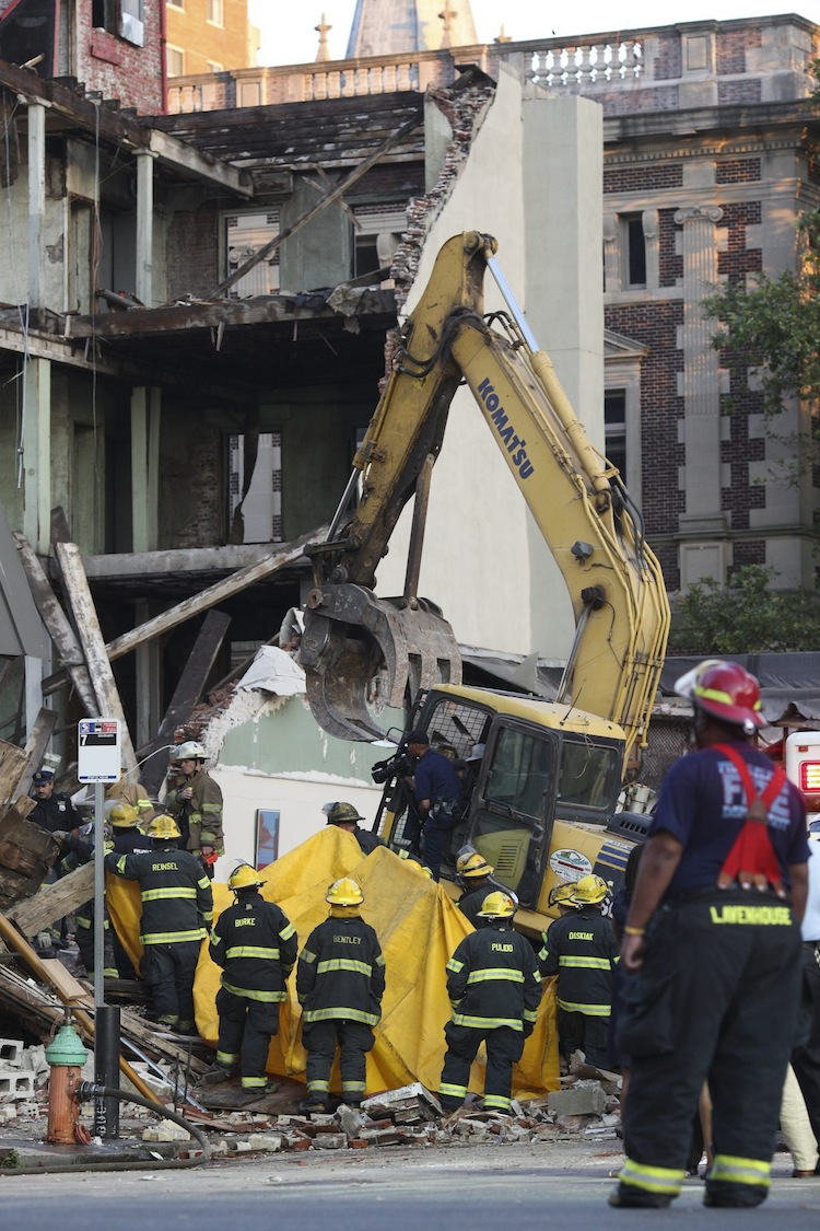 Philadelphia firefighters bring out a tarp to block the view as a body is removed from the rubble. (Andrew Renneisen / The Associated Press)