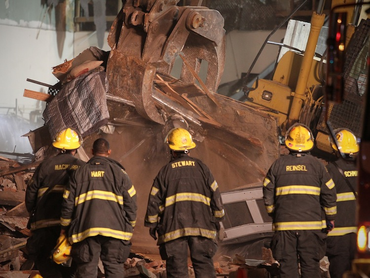Firefighters watch as the crane pulls debris away from the the site of the collapsed building on Wednesday night.
