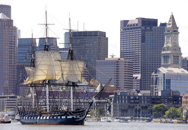 FILE - In this Aug. 29, 2014, file photo, the USS Constitution is nicknamed Old Ironsides the U.S. Navy's oldest commissioned ship that is still afloat, is towed through Boston Harbor past Boston's financial district skyline with its topsails unfurled. The warship officially closed Monday, April 27, 2015, and will partly reopen June 9, before entering dry dock near its berth on May 19 for a multi-year restoration project. (AP Photo/Stephan Savoia, File)