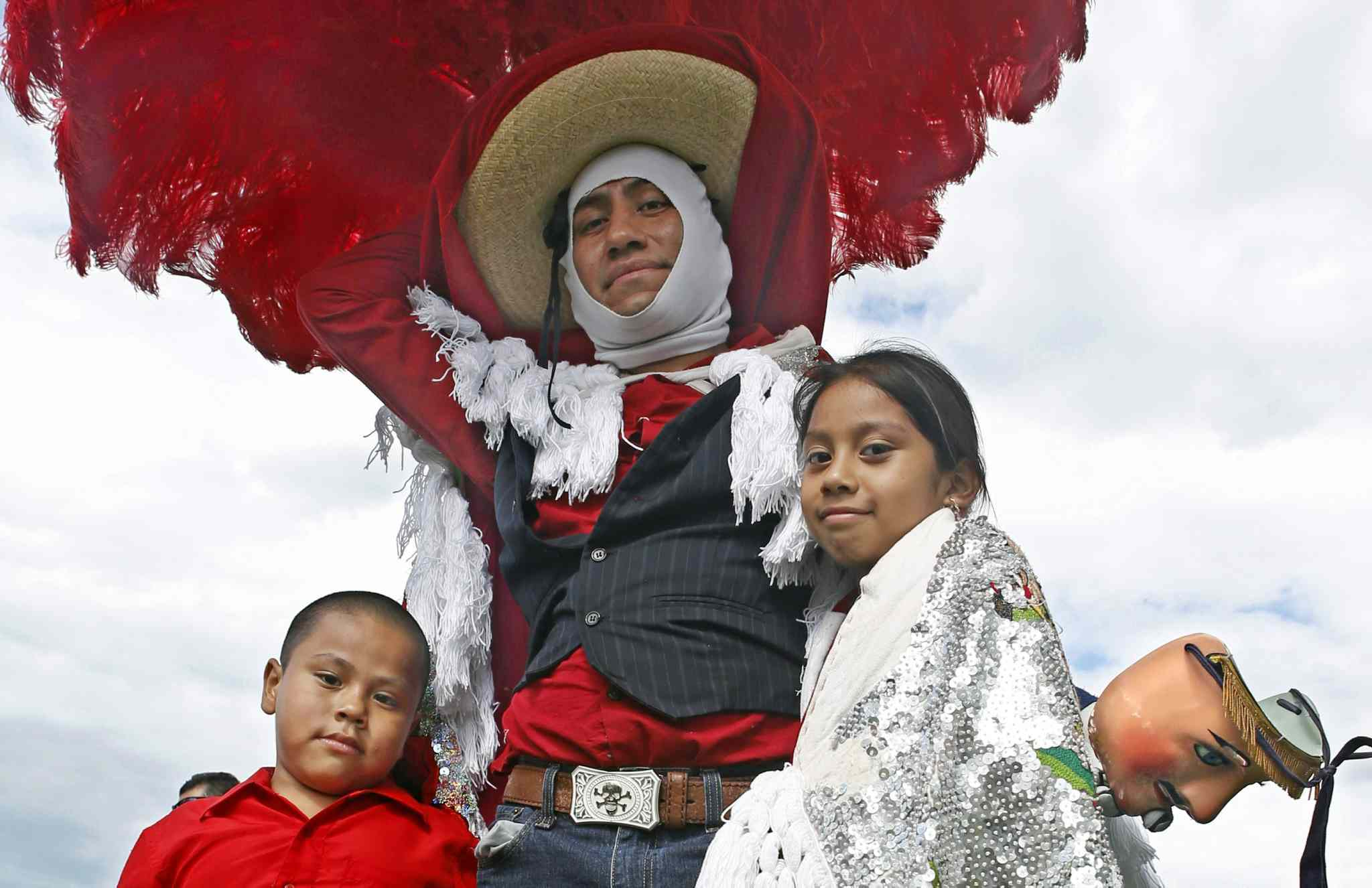 Mario Perez, 30, poses for a photo with his children Michael, 6, and Emily, 7, at a park in the Brooklyn borough of New York. At the park costumed dancers celebrated a festival from their home state of Tlaxcala, Mexico. Being a good dad, Perez said,