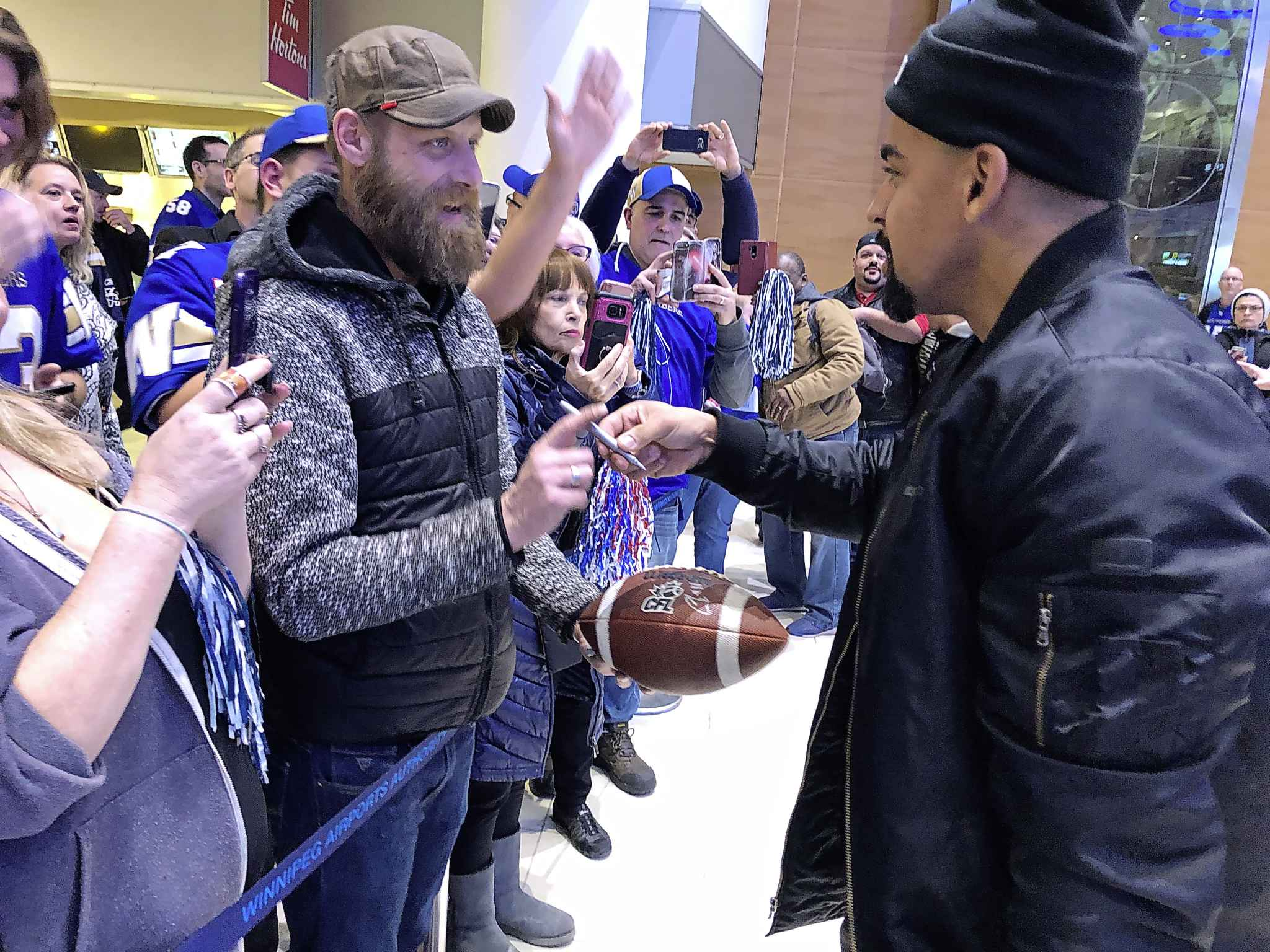 Winnipeg Blue Bombers running back Andrew Harris signs a football for a fan at James Richardson International Airport on Monday.