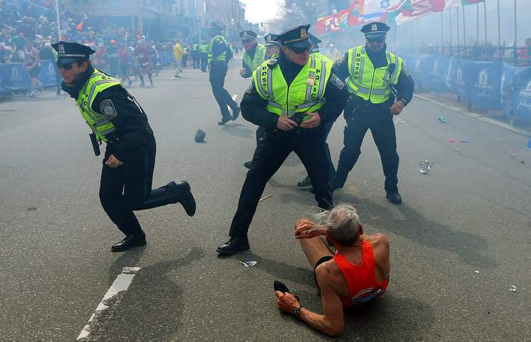 Police officers react to a second explosion at the finish line of the Boston Marathon in Boston, Monday, April 15, 2013. (AP Photo / The Boston Globe, John Tlumacki)