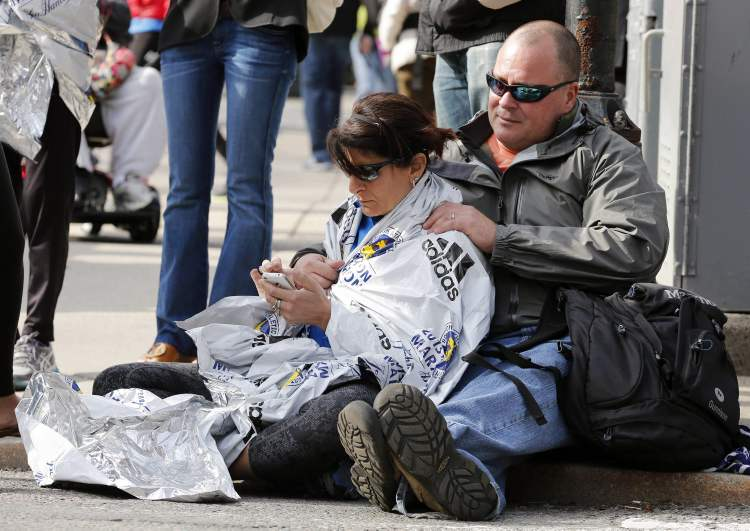 Chris Darmody, right, holds his wife Sue in Boston, Monday, April 15, 2013. Chris says he was waiting for Sue when an explosion detonated near his location at the finish line of the Boston Marathon. The couple were later reunited after all runners were diverted from the course.