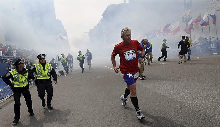 A Boston Marathon competitor and Boston police run from the area of an explosion near the finish line in Boston, Monday, April 15, 2013.
