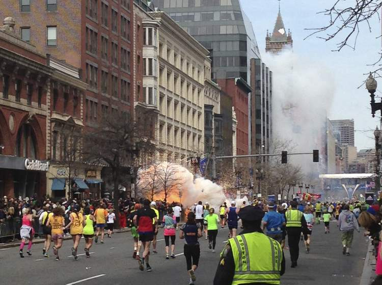 Runners continue to run towards the finish line of the Boston Marathon as an explosion erupts near the finish line of the race in Boston, Massachusetts, April 15, 2013.