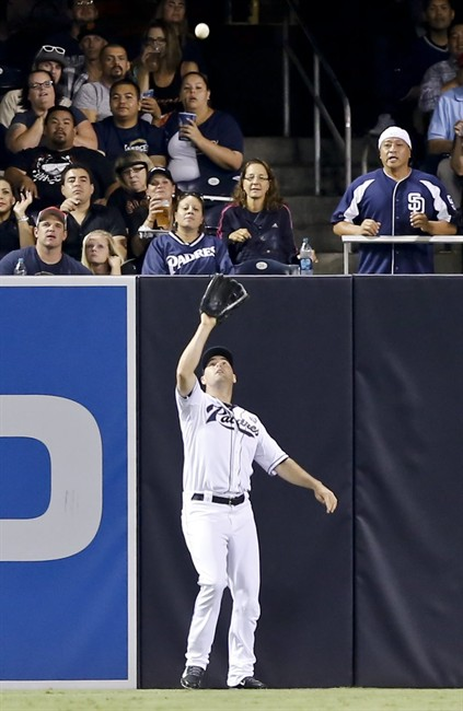 San Diego Padres left fielder Seth Smith makes the catch on the warning track on a fly ball by San Francisco Giants' Brandon Crawford during the fifth inning of a baseball game Friday, Sept. 19, 2014, in San Diego. (AP Photo/Don Boomer)