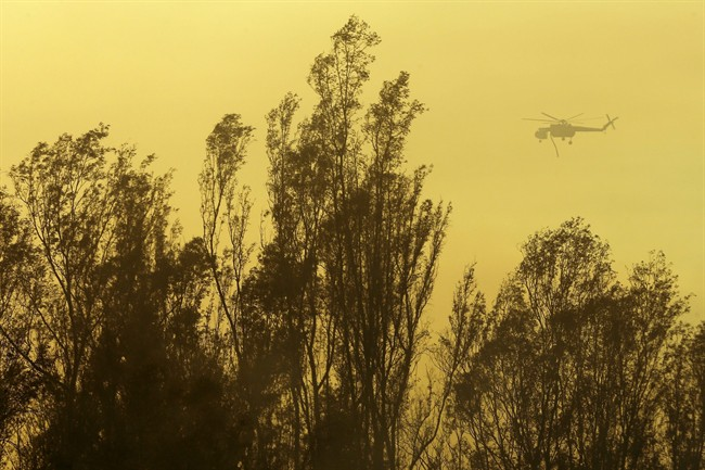 A helicopter transporting water flies over trees during a wildfire Thursday, May 15, 2014, in Escondido, Calif. One of the nine fires burning in San Diego County suddenly flared Thursday afternoon and burned close to homes, trigging thousands of new evacuation orders.(AP Photo/Gregory Bull)