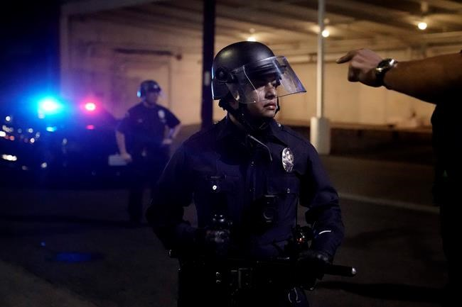 A protestor gestures towards a police official on Election Day, Tuesday, Nov. 3, 2020, in Los Angeles. (AP Photo/Jae C. Hong)