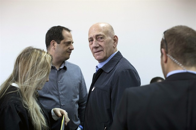 Former Israeli Prime Minister Ehud Olmert, center, waits in a courtroom before a verdict in Jerusalem's District Court on Monday, March 30, 2015. The court later found Olmert guilty of accepting bribes in a retrial of corruption charges. (AP Photo/Abir Sultan, Pool)