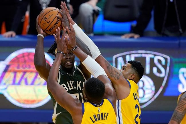 Milwaukee Bucks guard Jrue Holiday, rear, is defended by Golden State Warriors center Kevon Looney, bottom, and forward Kent Bazemore during the second half of an NBA basketball game in San Francisco, Tuesday, April 6, 2021. (AP Photo/Jeff Chiu)
