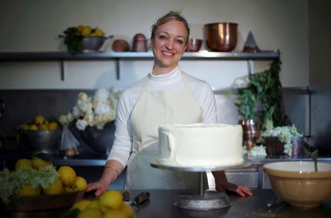 Claire Ptak, owner of Violet Bakery poses for a photograph with a tier of the cake for the wedding of Britain's Prince Harry and Meghan Markle in the kitchens at Buckingham Palace in London, Thursday May 17, 2018, ahead of their nuptials on Saturday. (Hannah McKay/Pool Photo via AP)