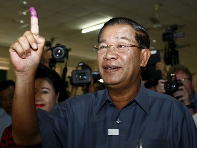 Cambodian Prime Minister Hun Sen shows his inked finger after voting at a polling station in Takhmau town, south of Phnom Penh, Cambodia, on July 28.
