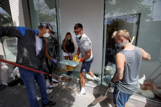 Volunteers pick up glass from a damaged The Gap store Monday, June 1, 2020, in Santa Monica, Calif., a day after unrest and protests over the death of George Floyd, a black man who died in police custody in Minneapolis on May 25. (AP Photo/Marcio Jose Sanchez)