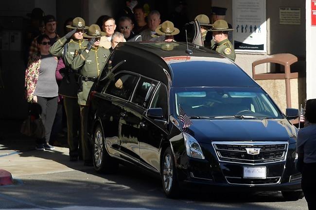 """An honor guard salutes the body of Ventura County Sheriff's Department Sgt. Ron Helus before it departs the Los Robles Regional Medical Center Thursday, Nov. 8, 2018, in Thousand Oaks, Calif. Helus was killed after a gunman opened fire the night before inside a country dance bar crowded with hundreds of people on """"college night."""" (AP Photo/Mark J. Terrill)"""