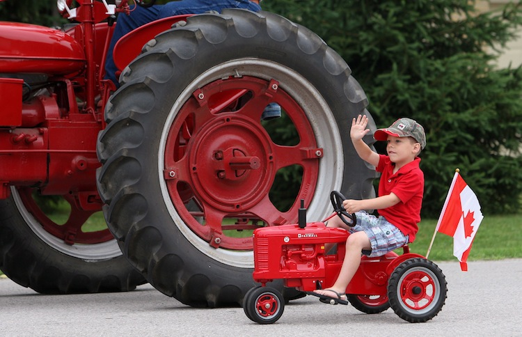 Five-year-old Logan Vanos pedals his mini-tractor beside his great-uncle Frank Roks in the Canada Day parade in the village of Komoka, Ontario, west of London. (Dave Chidley / The Canadian Press)