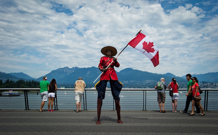 Dressed a Royal Canadian Mounted Police officer, Stephane Delage carries a Canadian flag while on stilts as he entertains the crowd in Vancouver. (Darryl Dyck / The Canadian Press)