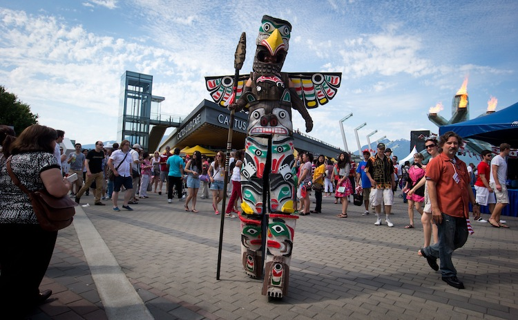 Chantal Limoges walks on stilts while dressed as a totem pole as she entertains the crowd during Canada Day festivities in Vancouver, B.C. (Darryl Dyck / The Canadian Press)