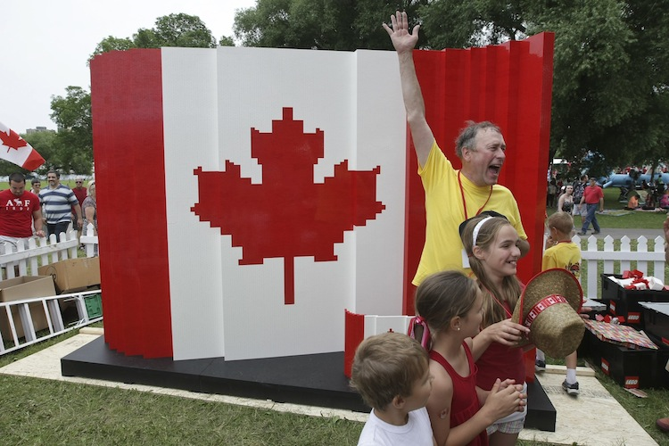 Master model builder Dan Steininger celebrates with kids after the last brick was laid on his piece during the Canada Day LEGO Flag Build at Parc Jacques-Cartier Park in Gatineau, Quebec. The flag is made out of 128,000 LEGO bricks. (Francis Vachon / AP Images for LEGO Systems, Inc.)