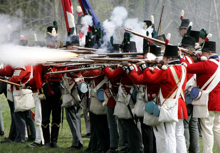 Re-enactors portraying British soldiers fire their muskets in a restaging of a War of 1812 battle near an actual battle site west of London, Ont.