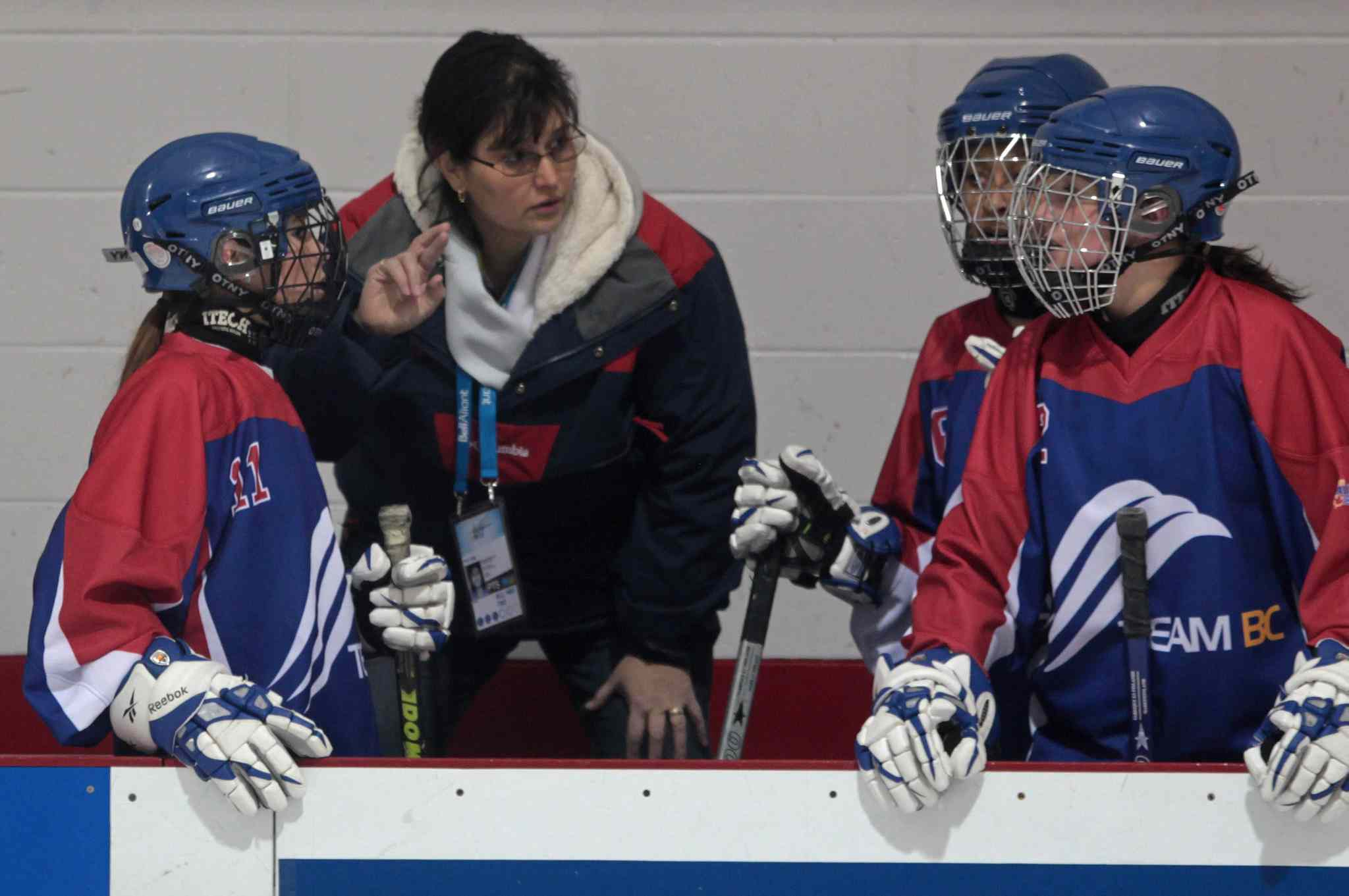 Elizabeth Dagg (left), a deaf ringette player, watches as her mother, Nora, relays her teammate's speech in sign language at the 2011 Canada Winter Games. Manitoba's Sport Secretariat has agreed to pay up to $40,000 per year so deaf children can communicate with coaches and game officials.