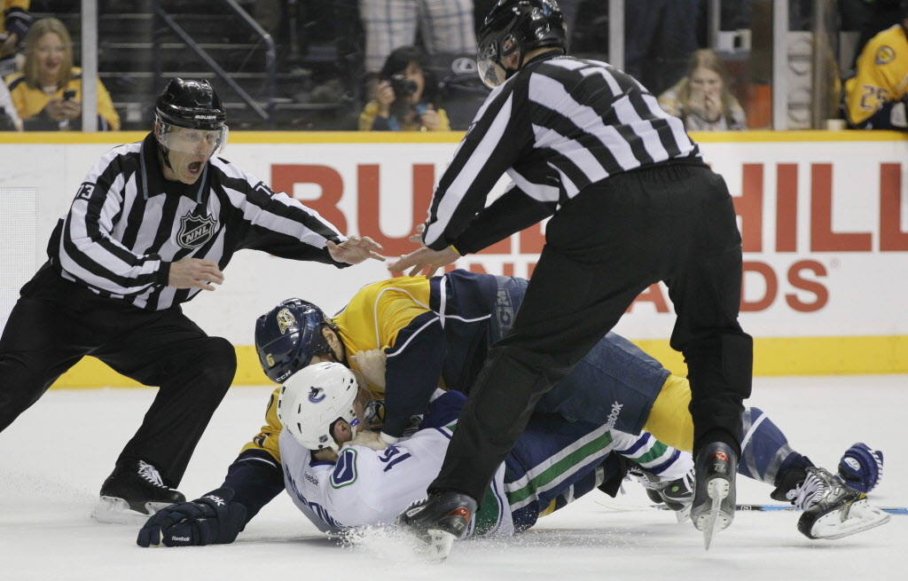Linesmen Vaughan Rody, left, and Tim Nowak, right, break up a fight between Vancouver Canucks right wing Alex Burrows, bottom, and Nashville Predators defenseman Shea Weber in the second period of an NHL hockey game.