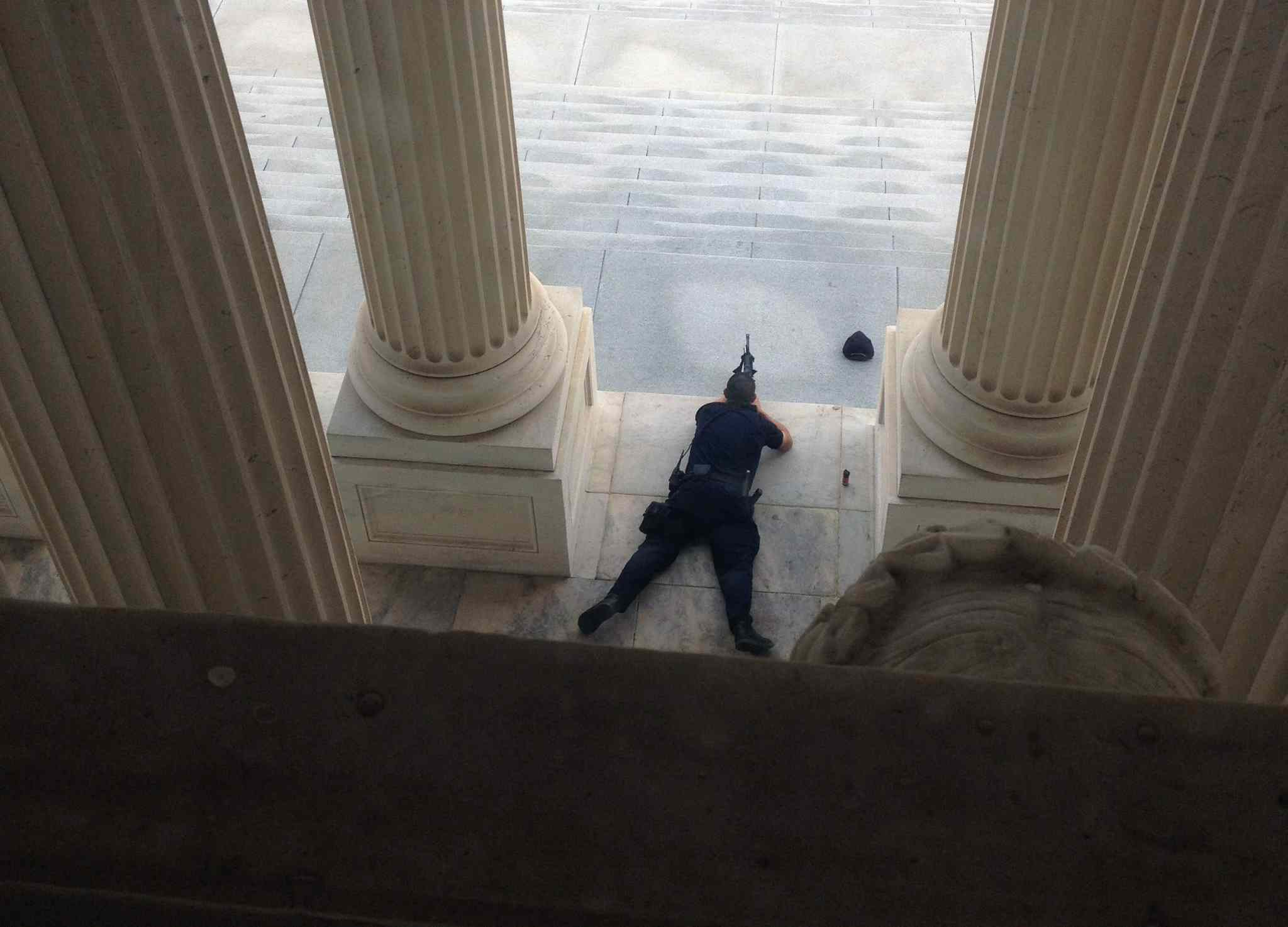 A U.S. Capitol police officer lies on the steps of the Senate with a gun drawn in response to a report of shots fired Thursday. The entire complex was locked down.