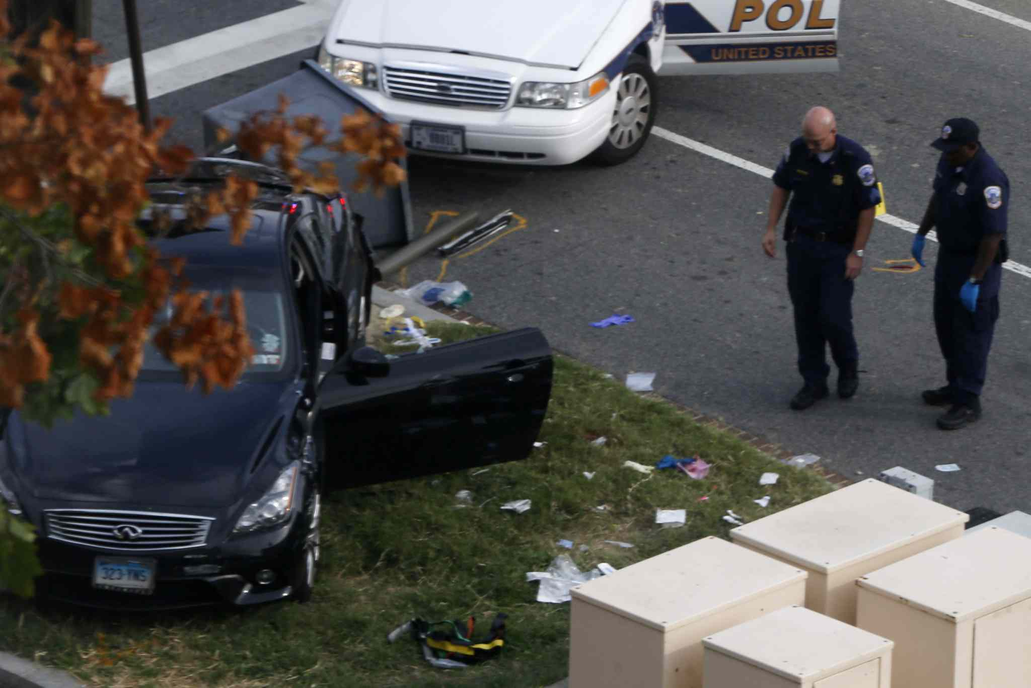 Capitol Hill police officers inspect a vehicle after the collision and shooting.