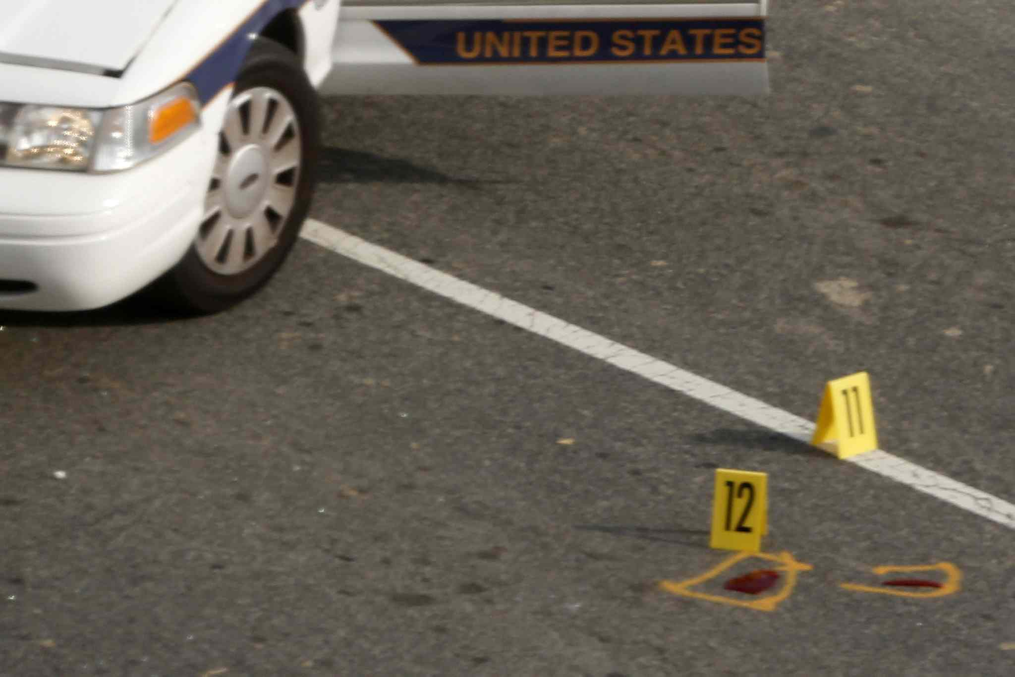 Evidence markers are placed near a Capitol police car.