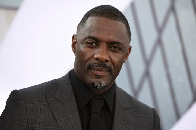 """FILE - In this July 13, 2019, file photo, Idris Elba arrives at the Los Angeles premiere of """"Fast & Furious Presents: Hobbs & Shaw."""" Elba said in an Instagram post on Monday, March 16, 2020 that he has tested positive for the coronavirus and is isolating himself, but has shown no symptoms yet. (Photo by Jordan Strauss/Invision/AP, File)"""